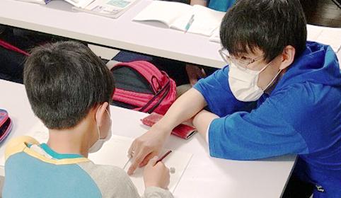勉強を教えている先生と生徒の写真