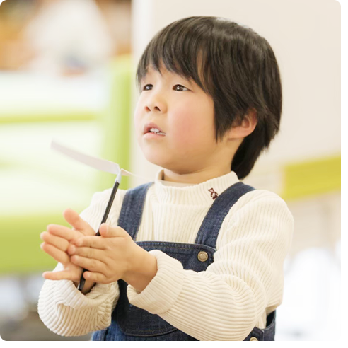 工作した竹とんぼを飛ばそうとしている少年の写真